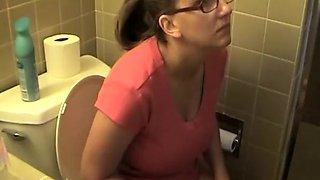 Busty woman in bathroom toilet peeing