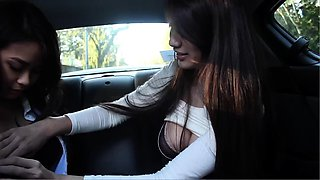 Two stacked brunettes engage in hot lesbian fun in the car