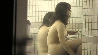 Voyeur spies on attractive Japanese babes taking a shower